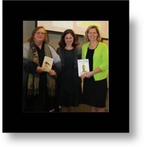 Shelly Willis of FESS, Ashley Merryman and Jennifer Williamson Forster show off two of the books co-authored by Ashley.